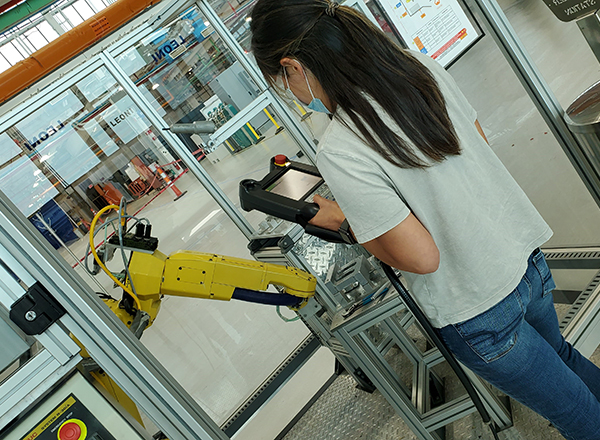 HFC student/GM apprentice Sylvia Tran operates a robotic arm during a demonstration.