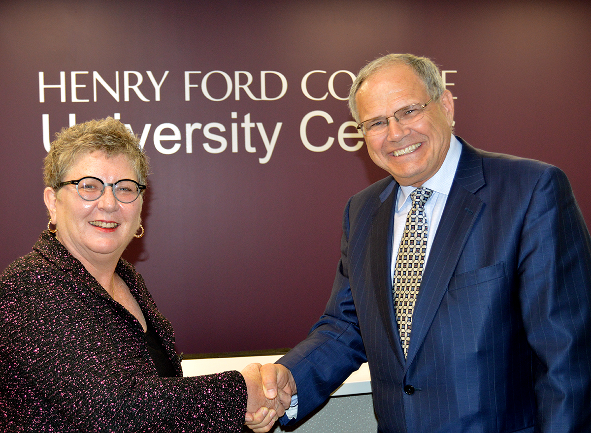 HFC President Stanley Jensen shaking hands with former Eastern Michigan University interim president Kim Schatzel in July 2015