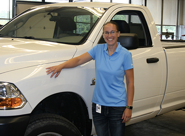 Ashley Smith, HFC's first automotive faculty member, poses with a pick-up truck