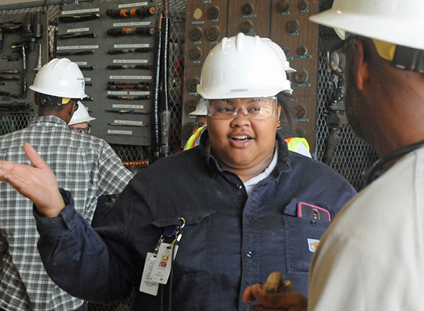 Female student in hardhat facing camera, speaking to a man facing away from camera