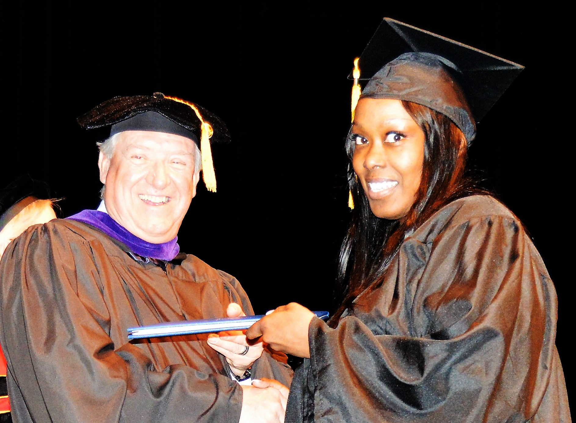 Interim President John Satkowski gives a graduate her diploma
