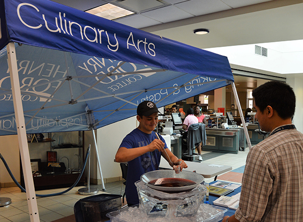 A student samples the offerings of HFC's Culinary Arts program at Welcome Back Days.