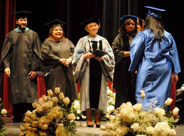 Dr. Mee (center) awards an HFCC student her degree.