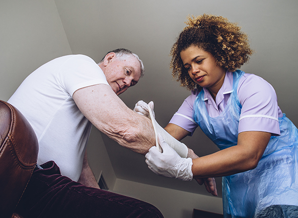 Medical assistant wearing gloves pulls a compression sleeve onto a patient's arm