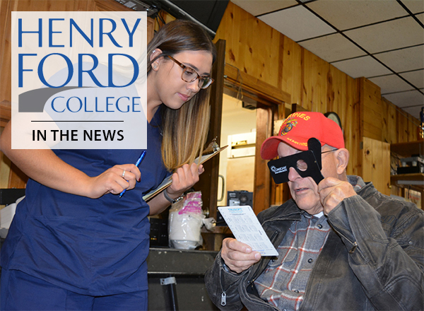 Female ophthalmic tech student standing near veteran undergoing eye exam