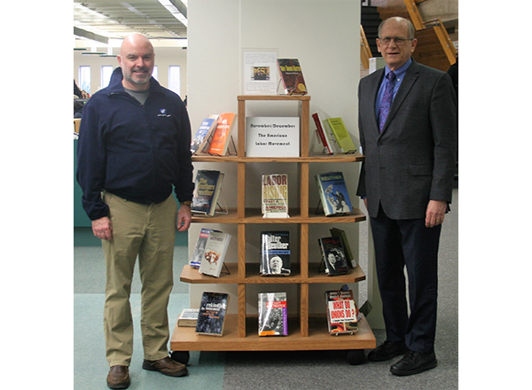 Eric Rader and John McDonald stand next to a book display