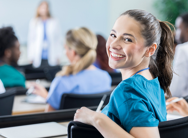 Female student turning around in her chair to smile at the camera