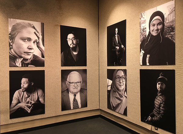 Eight large individual portraits displayed on the gallery wall at Sisson
