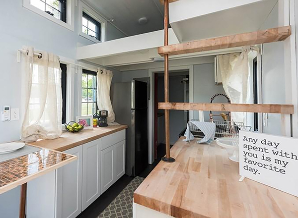 Interior of tiny house, all-white interior with loft, light wood butcher-block counters
