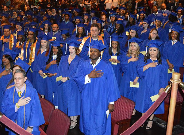 HFC graduates, wearing blue graduation gowns, standing for the National Anthem