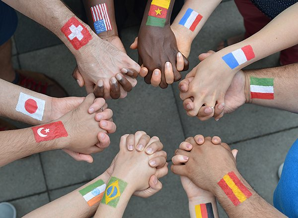 Photo of people holding hands, different international flags