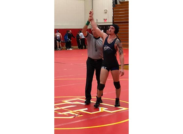 Dominic Mancina on the wrestling mat, arm raised in victory