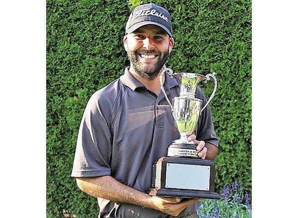 photo of Kieronski holding up golf trophy