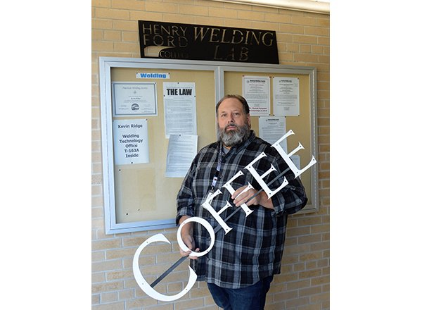 Photo of Ridge holding his coffee sign